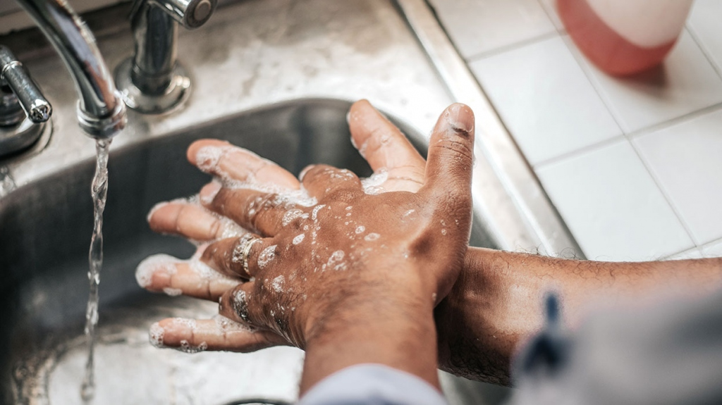 Man washing his hands thoroughly in the sink to protect from COVID-19. However, his hands are very dry.